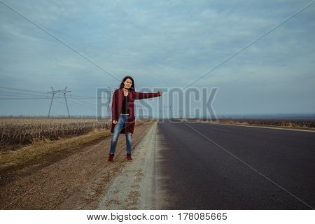 young woman travel with hitch-hiking couldy weather