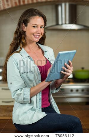 Portrait of woman sitting on worktop and using tablet