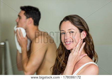 Beautiful woman smiling at camera and man wiping his face behind her