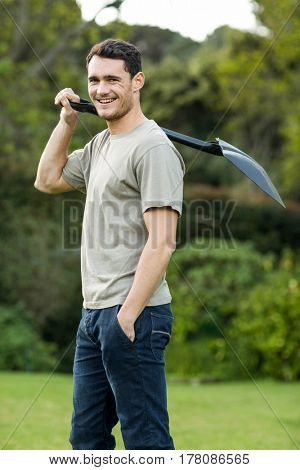 Portrait of young man standing in garden with a gardening shovel in garden