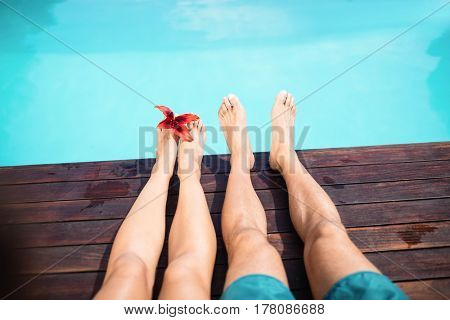 Couple bare feet against swimming pool on a sunny day