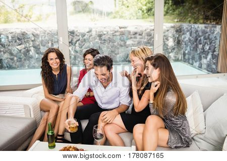 Happy man sitting with woman and having fun at party