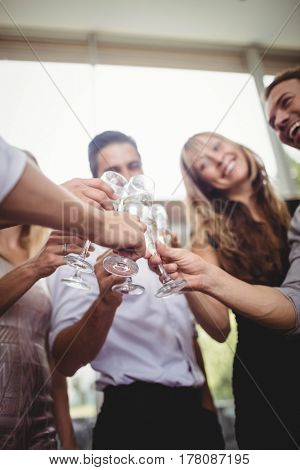 Group of friends smiling and toasting glasses of champagne at party