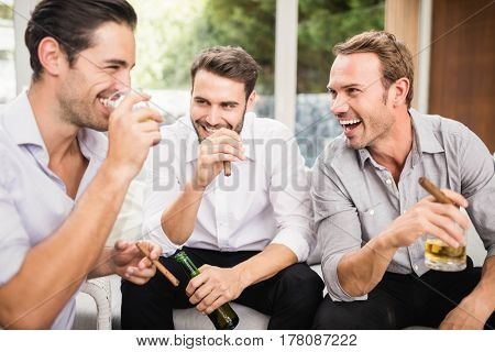 Group of men smoking and drinking while discussing