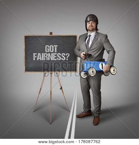 Got fairness text on blackboard with businessman and toy car