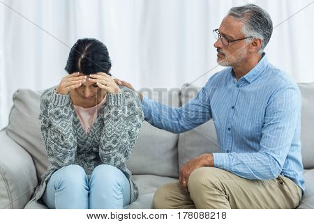 Therapist consoling a woman at home