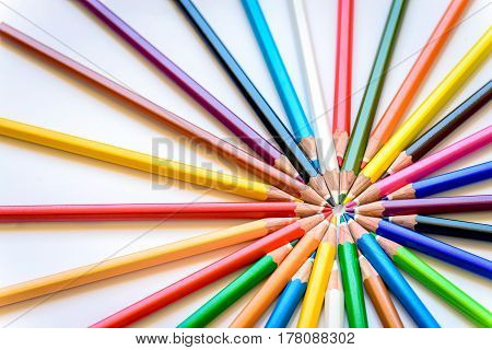 Sharp colorful pencils pointing to each other forming logical center