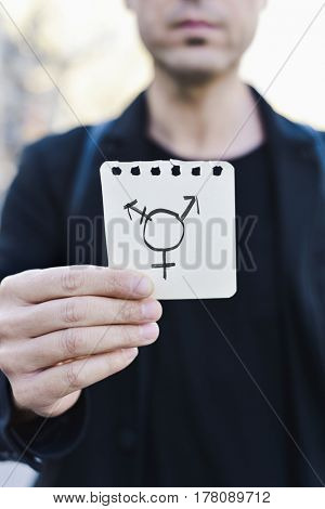 closeup of a young Caucasian man in the street showing a piece of paper with a transgender symbol drawn in it