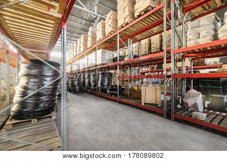 Warehouse industrial goods. Large long racks. Cardboard boxes and twisted plastic tube.