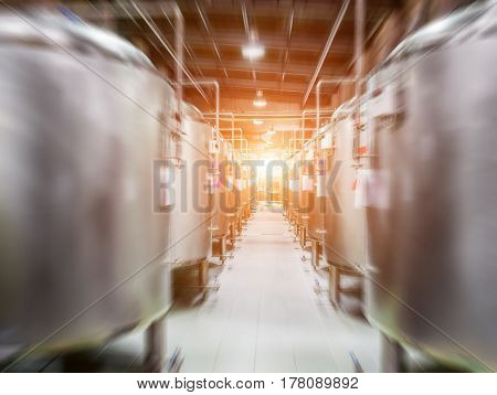 Modern Beer Factory. Steel tanks for beer fermentation and storage. Motion blur effect, sunlight