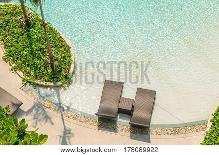 Beach chairs in luxury swimming pool at tropical hotel resort relaxing and leisure time in the pool. Top view.