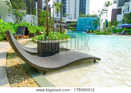PATTAYA THAILAND - April 20 2016: Beach chairs in luxury swimming pool at tropical hotel resort relaxing and leisure time in the pool. Pattaya Thailand April 20 2016