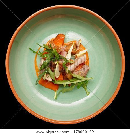 Game bird fillet with sweet potato mash and mushrooms in green porcelain plate, isolated on black background
