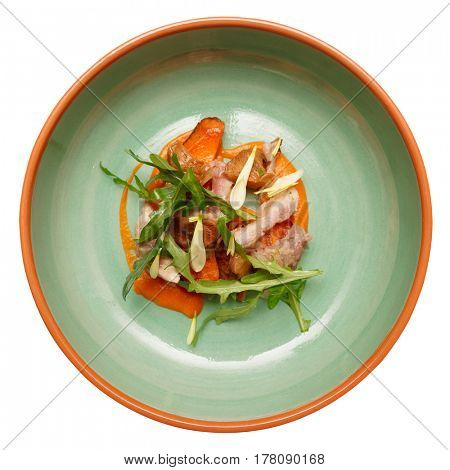 Game bird fillet with sweet potato mash and mushrooms in green porcelain plate, isolated on white background