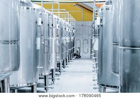 Row of steel tanks for storage and fermentation of beer. Toning the image.