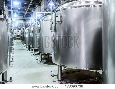 Modern Beer Factory. Rows of steel tanks for beer fermentation and maturation. Blue spot light effect