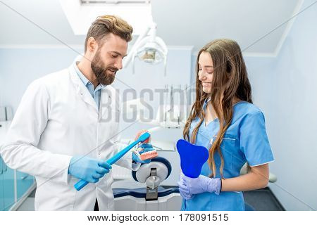 Handsome dentist showing how to brush teeth on artificial jaw to the young female student at the dental office