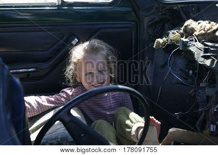 Little smiling girl sitting in an old broken car