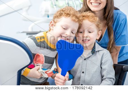 Young boys looking at the mirror with toothy smile sitting with dentist at the dental office