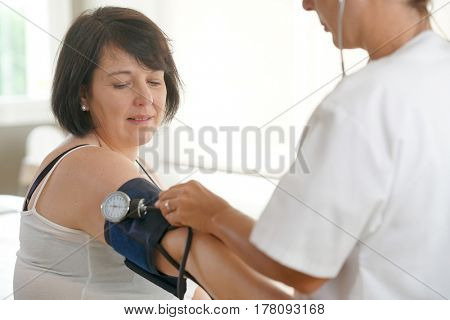 Mature woman at the doctor, controlling blood pressure