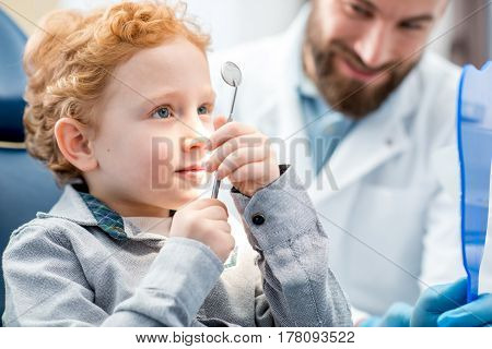 Young excited boy looking at the dental mirror sitting on the chair with dentist at the dental office