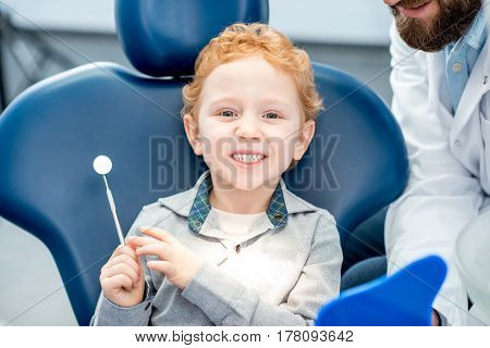Young excited boy looking at the dental mirror sitting on the chair at the dental office