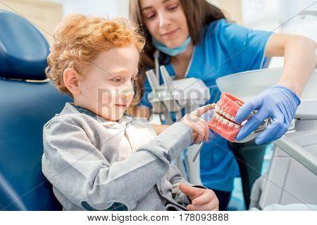 Female dentist showing the young boy artificial jaw at the dental office