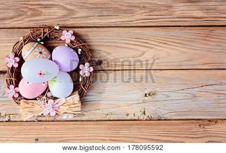 Easter Eggs In Nest On Rustic Wooden Background