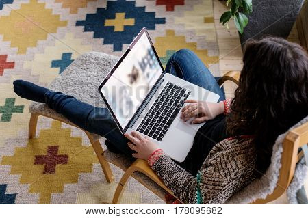 Woman working on laptop in home workplace