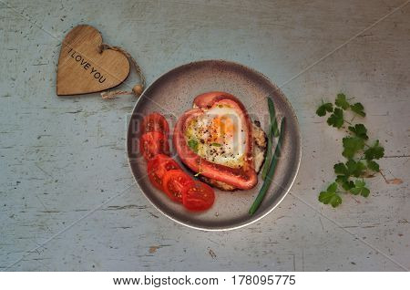 Sausages in form of hearts scrambled eggs and parsley on color plate on wooden background
