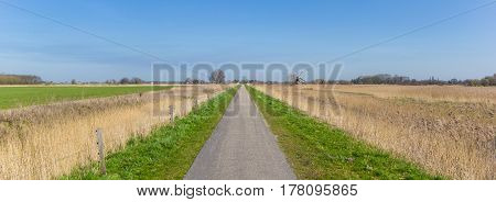 Panorama of a narrow road through the countryside in Groningen The Netherlands