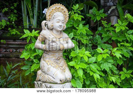 Girl statue in white stone in Balinese style on the background of greenery Indonesia