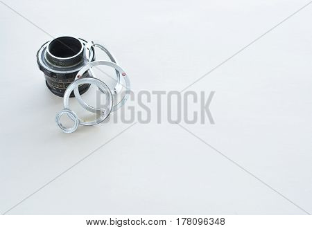 Details of the old manual lens, free space. A disassembled lens lined up in a row on a white background. Technical background. Service center.