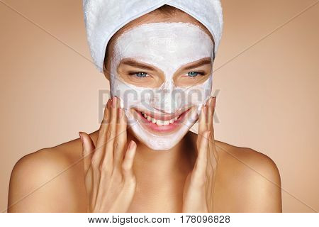 Attractive young woman with face mask. Portrait of happy woman with towel on her head on beige background. Grooming himself