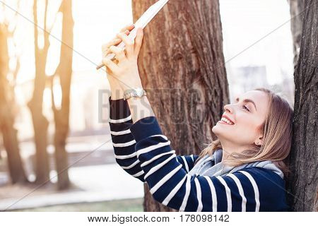 Young attractive girl is posing while photographing herself on modern tablet for social network picture during recreation time in park charming blonde female is making self portrait with digital tablet camera