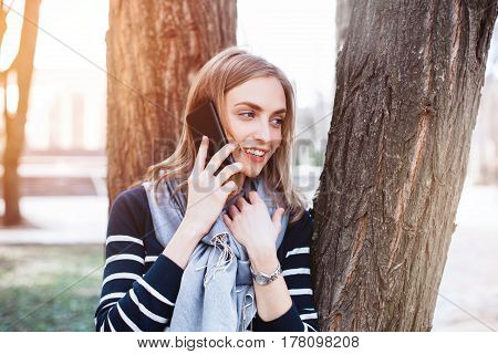 Happy hipster girl having pleasant mobile phone conversation with boyfriend while is walks in spring park smiling female talks on smarphone and relaxes outdoors during free time