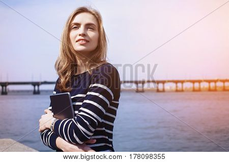 Young beautiful girl thinking about something after reading electronic book on her portable touch pad dreaming female looking away while standing with digital tablet near river