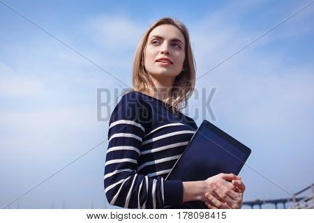 Young beautiful girl thinking about something after reading electronic book on her portable touch pad dreaming female looking away while standing with digital tablet