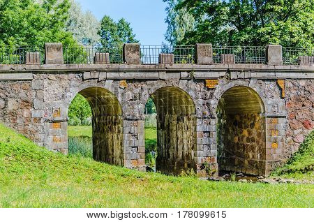 Old arched stone bridge on the background of green meadows in Oranienbaum Park in Russia.
