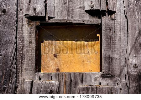 Wooden background. Close-up window closed with piece of plywood in wall of old wooden planks.