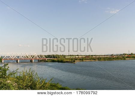 Railway bridge through the river Volga and freight train is moving to it in summer day in Syzran Russia.