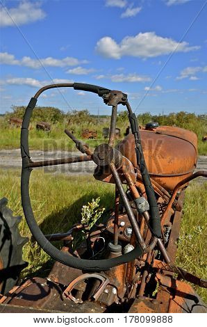 An old tractor with a bent steering wheel is left in a salvage and junkyard