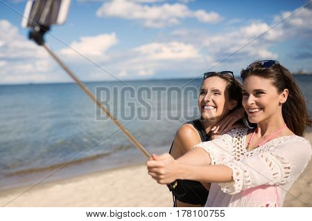 Two Pretty Girls Taking Themselves Photo On Beach