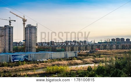 Tianjin, China - Oct 31, 2016: Construction of new residential townhouses and high-rise apartments, outside of Tianjin City. Scene captured from within a High-Speed Rail (HSR) bullet train traveling at 300 km/h.