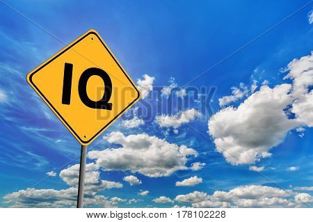 Background of blue sky with cumulus clouds and yellow road sign with text IQ