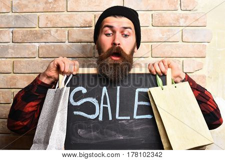 Bearded man long beard. Brutal caucasian surprised hipster with moustache holding shopping packages in red black checkered shirt and board with Sale inscription on beige brick wall studio background