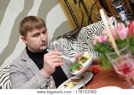Man takes appetizer from plate in a restaurant