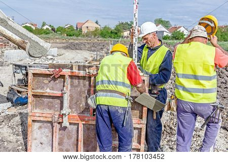 Zrenjanin Vojvodina Serbia - April 30 2015: Construction worker is holding leveling rod to help surveyor geodesist to measure position depth.