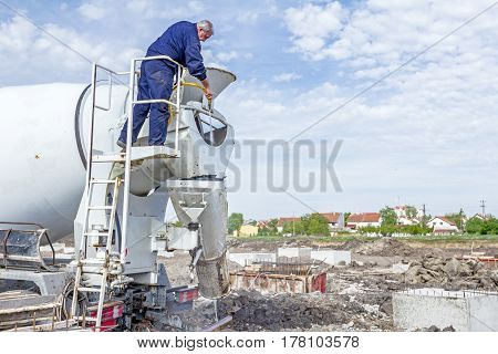 Zrenjanin Vojvodina Serbia - April 30 2015: Driver is washing mixer truck with water jet after concrete casting.