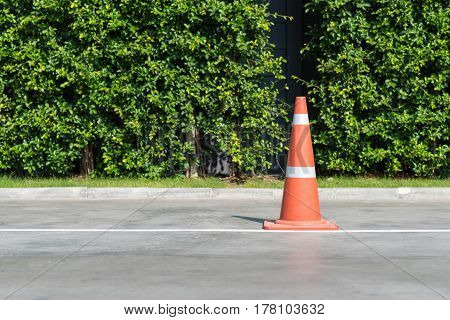 Single orange traffic cone on concrete street road with small park in background